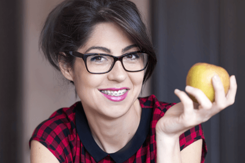 lady in glasses holding apple smiling